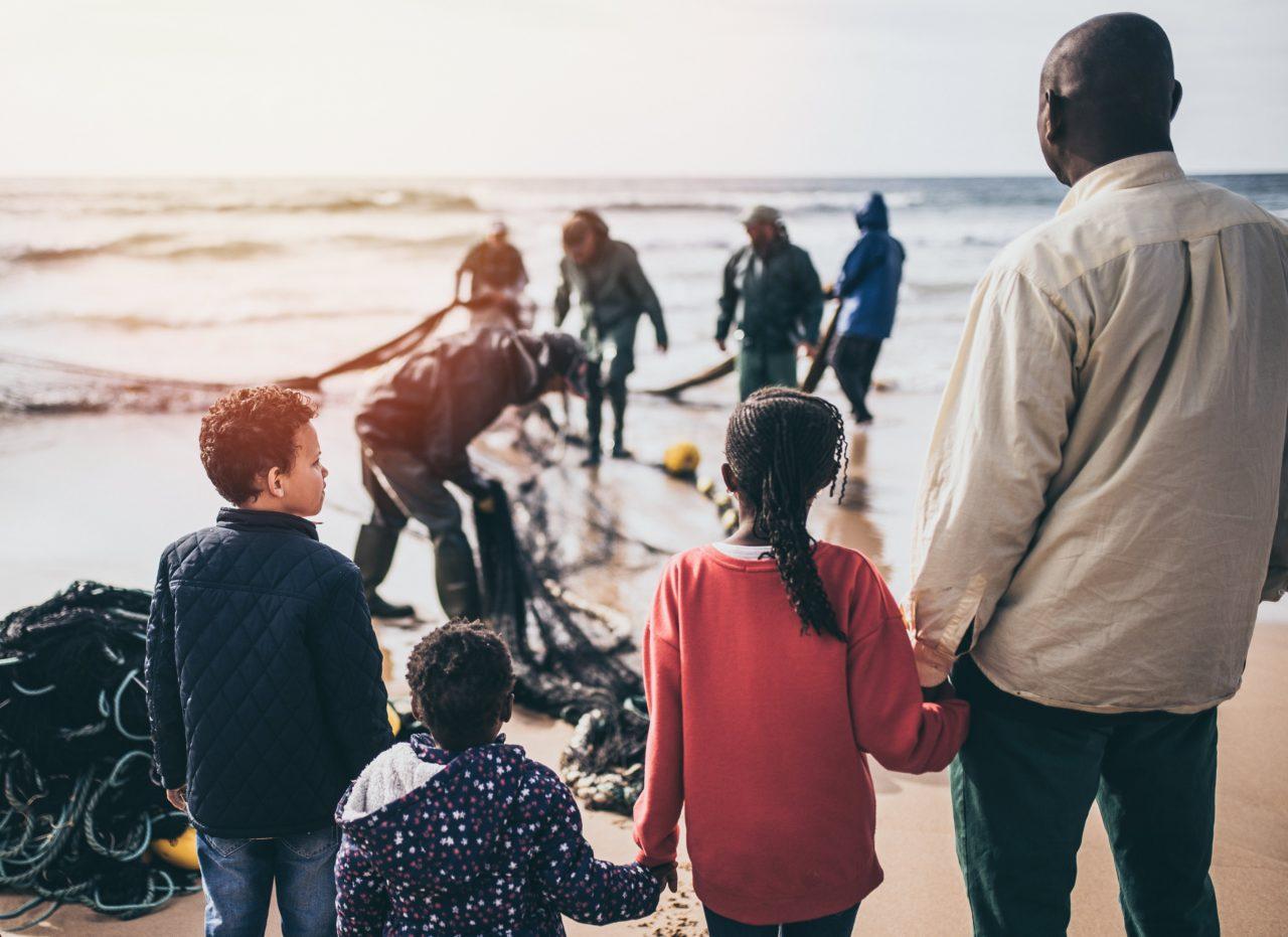 Flüchtlinge stehen am Meer